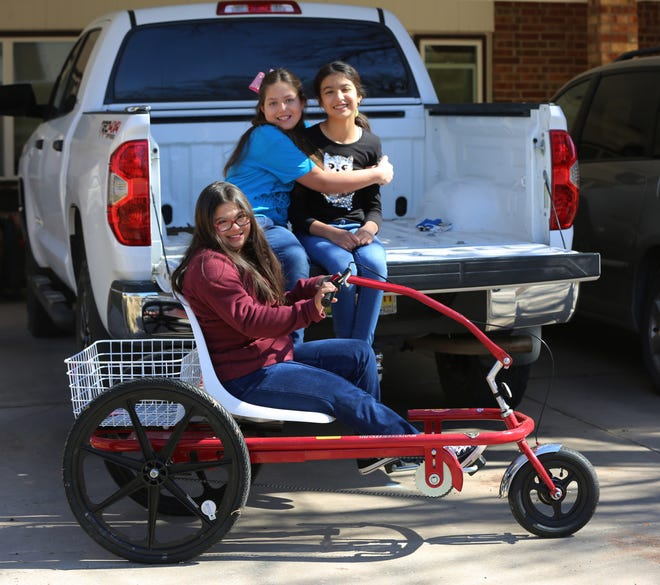 Zia Middle School student Grace Holguin, 14, on her special needs trike, and her sisters Eve, 9, and Sophia, 10, pictured Friday, Feb. 19, 2021. In late January, Grace's brand new trike was stolen from her family's home. It was later recovered.