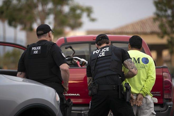 Agentes del Servicio de Control de Inmigración y Aduanas de Estados Unidos (ICE por sus siglas en inglés), detienen a un hombre durante un operativo en Escondido, California.