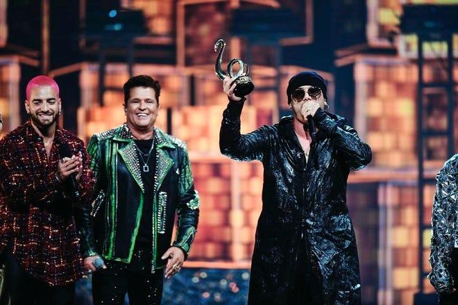 Fotografía cedida por Univison donde aparece el reguetonero puertorriqueño Wisin (d) mientras recibe un premio junto a los cantantes colombianos Maluma (i) y Carlos Vives (c), durante  la ceremonia de entrega de los premios Lo Nuestro 2021 en el American Airlines Arena de Miami, Florida.