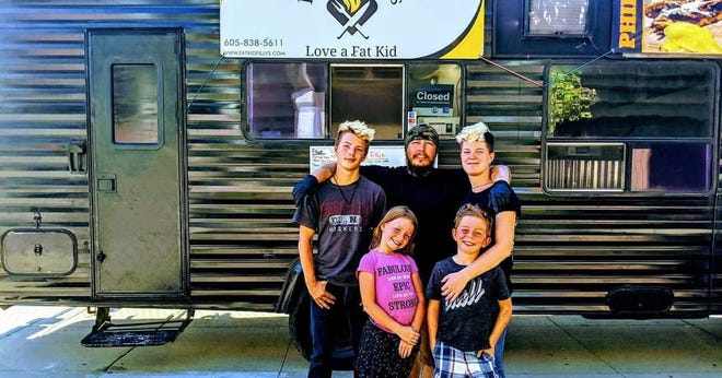 Cody (middle) and Amber (right) Sauers pose with their children in front of the Fat Kid Filly's food truck.