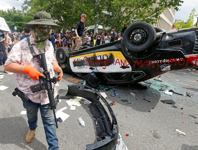 FILE - In this May 30, 2020, file photo, an armed protester walks past a flipped over police vehicle in Salt Lake City. A Utah legislative committee has passed a bill that would increase penalties and eliminate bail for rioting in response to last year's protests against police brutality and racial injustice. (AP Photo/Rick Bowmer, File)