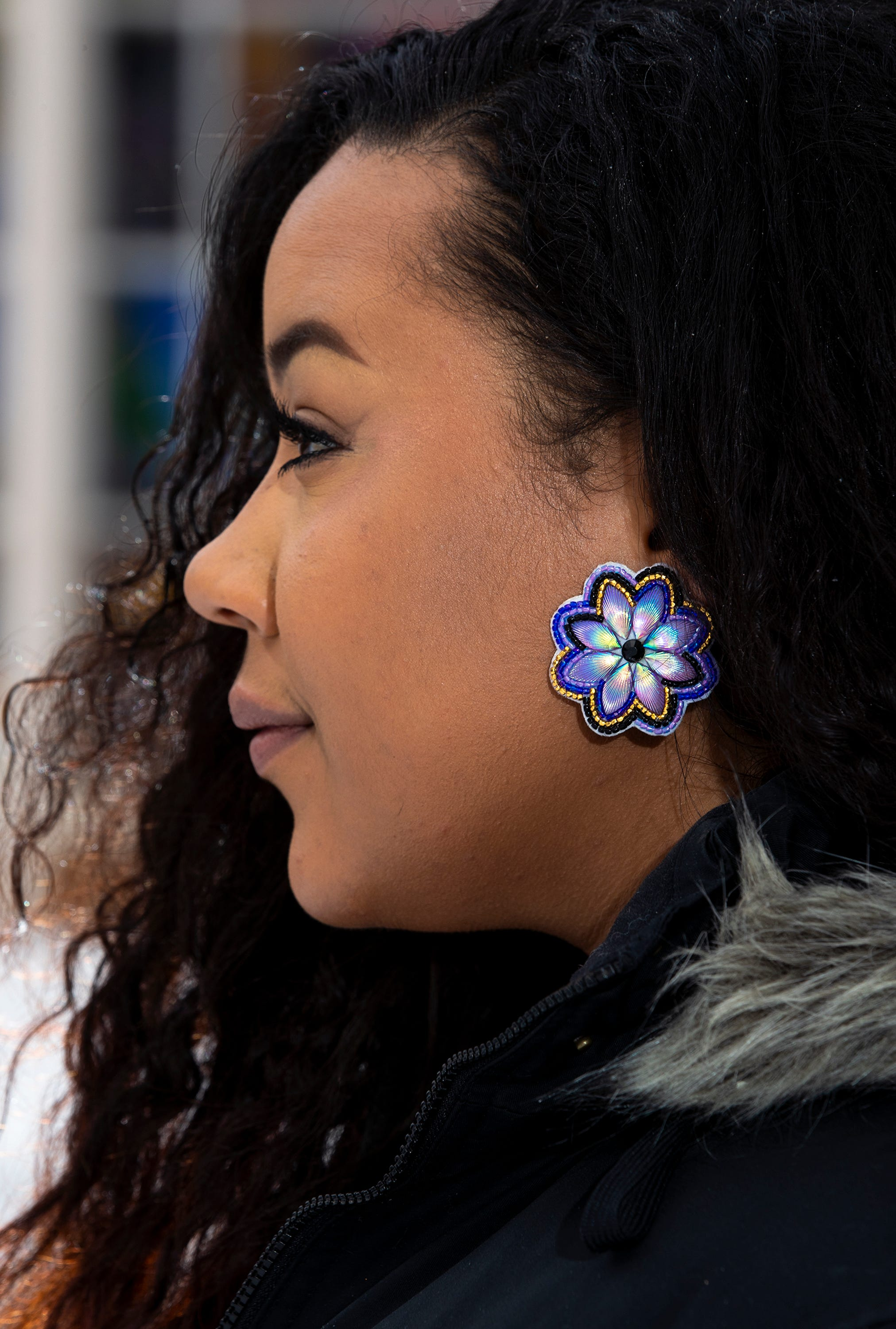 Aaliyah Coppadge, 23, displays her grandmother's Native American earrings as she poses for a portrait Feb. 19 at the intersection of Mcindoe Street and North Fourth Street in Wausau.