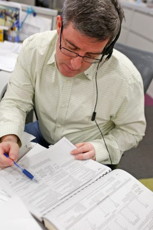 Rob Winton, a CPA with Citrin Cooperman in White Plains, reviews information during a tax hotline session at The Journal News office, March 1, 2014 in White Plains.