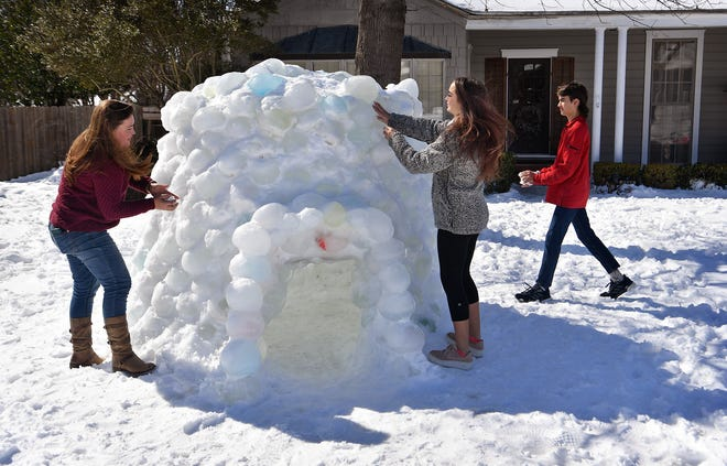 Catherine Earley and her kids, Hannah and Ethan Earley, pack snow into spaces in the igloo they created using frozen water balloons at their home on Lake Park Drive. This is the tenth year Earley and her husband, John, have built an igloo as a family project.