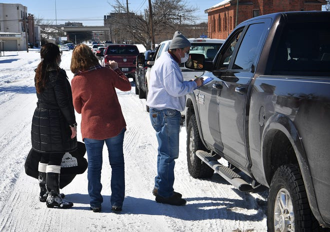Meals on Wheels volunteers talk with drivers as they resume meal deliveries Friday. Recent weather has affected regular deliveries.