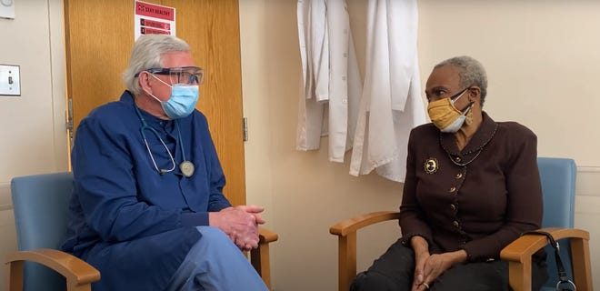 Jewelean Jackson, right, a patient at Community-University Health Care Center in Minnesota, chats with Dr. Chris Reif about the COVID-19 vaccine.