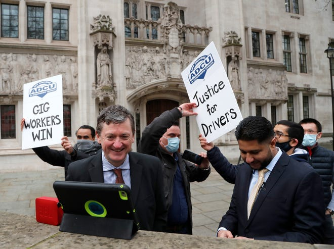 Uber drivers of the (ADCU), App Drivers & Couriers Union, celebrate as they listen to the court decision on a tablet computer outside the Supreme Court in London, Friday, Feb. 19, 2021.