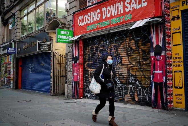 A pedestrian wearing a face mask walks past a shuttered souvenir shop on Oxford Street, central London, on Jan. 15, 2021.