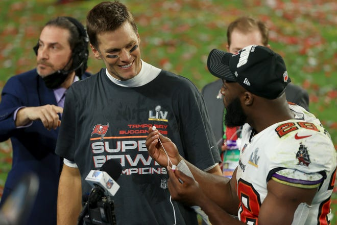 Tom Brady and Leonard Fournette celebrate after winning Super Bowl LV at Raymond James Stadium on February 07, 2021 in Tampa, Florida. The Buccaneers defeated the Chiefs 31-9.