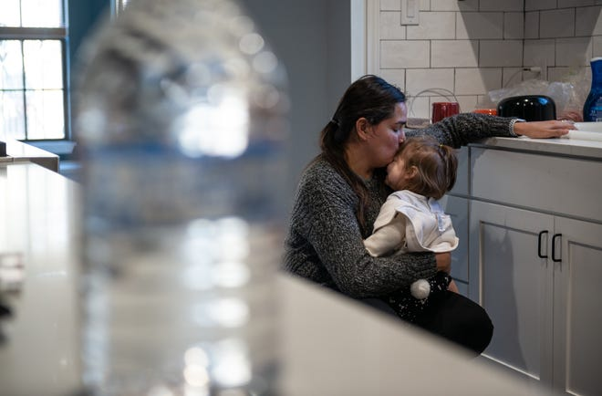 "Mary Holmes, 40, kisses one-year-old daughter Nara Holmes, Friday, Feb. 19. Nara has been especially attached to her mother after stressful interruptions in her schedule due to the arctic blast. Their Austin home lost power for 67 hours forcing them to stay at a friend's house. After returning home, their water started ""fizzling out"" and then completely shut off. Holmes brings water collected from work home to clean and cook with after boiling it."