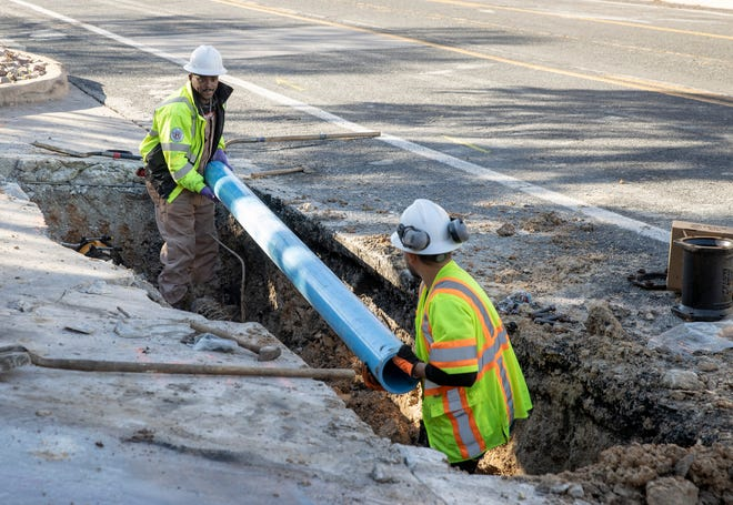 City of Austin Water Utility workers Joey Putman, left, and Salvador Tinajero repair a broken water main near 11th and Red River streets on  Feb. 19.