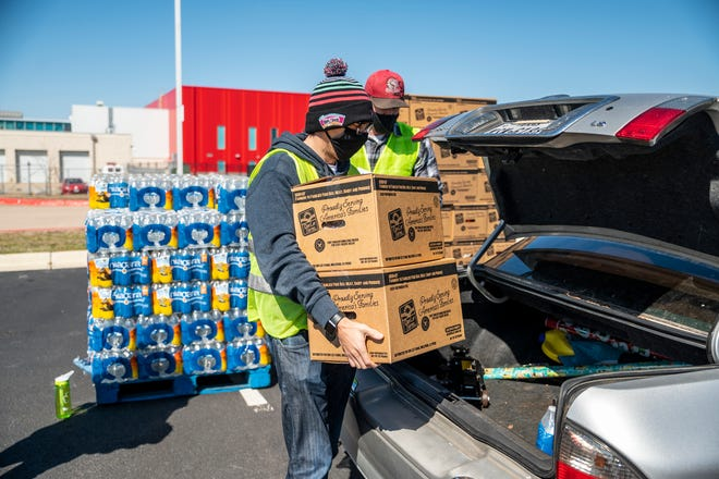 Sean Burg and Josh Morgan load up supplies in a car at a  Central Texas Food Bank event at Del Valle High School on Saturday. The drive-thru event offered food, water and milk in the aftermath of the winter storm that has left millions in Texas without clean drinking water.