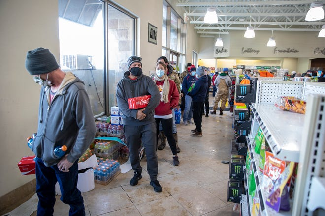People wait in line to buy food at a Timewise gas station in Pflugerville on Feb 16.
