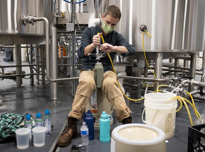 Will Jaquiss, the owner of Meanwhile Brewing Company, fills containers with water on Friday February 19, 2021, during a citywide boil water notice caused by the winter storm.   The brewery gave away all 4,000 gallons of their water to people in need on Thursday and Friday.