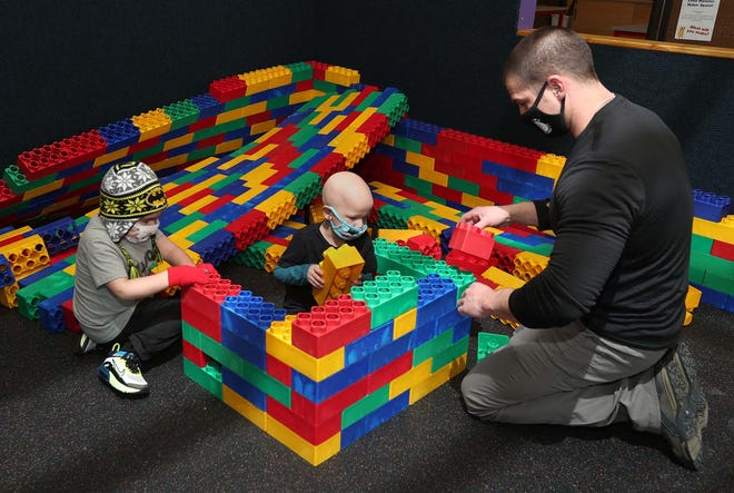 Mela Lemmon, 4, center, plays with the Jumbo Blocks with her father, Brock Lemmon, and her friend Philip Igo, 5, at the Akron Children's Museum on Saturday.