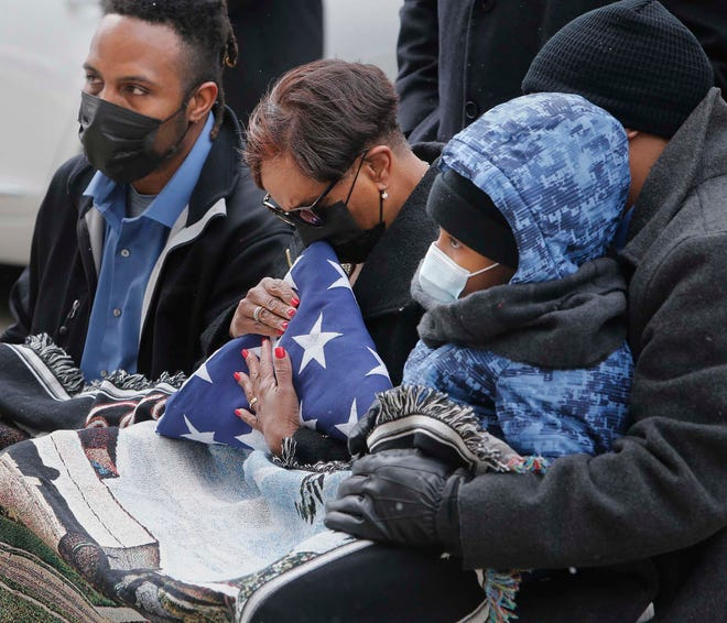 Lisa Stewart, the widow of Akron police officer Edward Stewart, embraces the U.S. flag that was presented to her by the Akron Police Department Honor Guard as she sits between sons Leland and Jason Stewart and her grandson during a brief memorial service Saturday in front of the Harold K. Stubbs Justice Center in Akron.