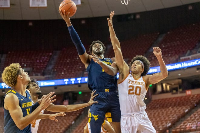 West Virginia forward Derek Culver goes to the basket over Texas forward Jericho Sims during the Mountaineers' 84-82 victory Saturday at the Erwin Center.