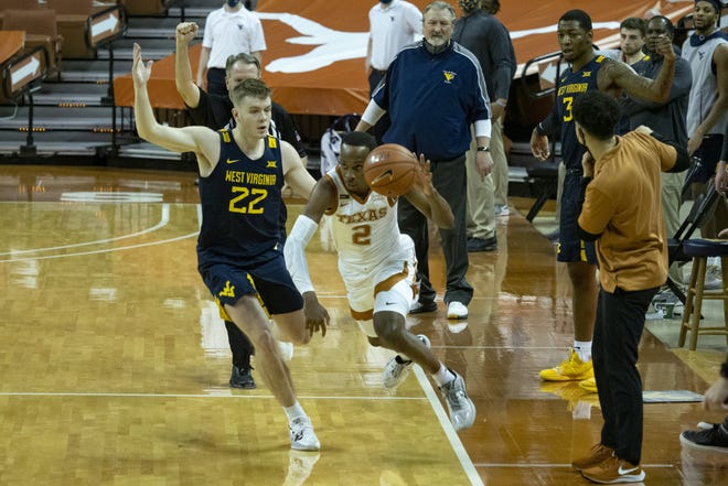 Texas guard Matt Coleman III is fouled by West Virginia guard Sean McNeil during Saturday's loss in Austin. Coleman and the Longhorns must regroup following the meltdown in which they squandered a 19-point lead.