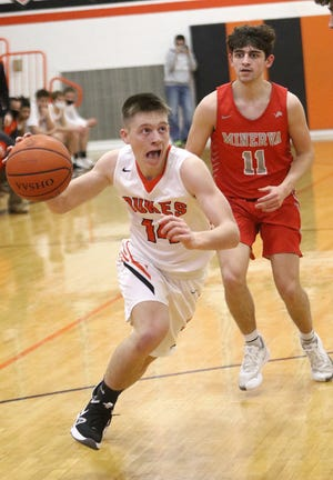 Marlington's Casey Miller, front, drives to the hoop defended by Minerva's Owen Swogger during action at Marlington High School Friday, February 19, 2021.