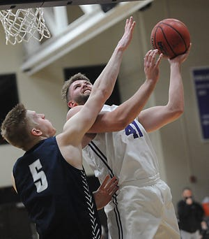 Mount Union's Logan Hill puts up a shot over Marietta's Tim Kreeger in an OAC game at the MAAC Friday, February 19, 2021.