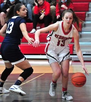 Loudonville's  Grace Vermilya (13) drives past Andrews Osborne's Deenah McFadden (13) during the Redbirds' 71-63 win Saturday at Loudonville High School.