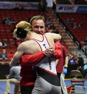 Gilbert head coach Scott Auderer embraces Tiger senior wrestler Cael Ihle after Ihle pinned Keokuk's Tate O'Shea at 126 pounds in the second round of Class 2A consolations Friday at the state wrestling tournament in Des Moines. The victory guaranteed Ihle, who nearly missed state with a shoulder injury, a spot on the meal stand.