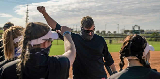 Lake-Sumter State College head softball coach Jay Miller joins his players in a pregame chant before Game 1 of a doubleheader Tuesday against South Florida State College at Legends Way Ballfields in Clermont. [PAUL RYAN / CORRESPONDENT]