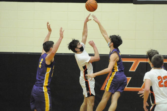 Blissfield seniors Nolan Savich (3) and Ty Wyman (2) defend Hudson's Rhys Mitchell during a LCAA game on February 11.