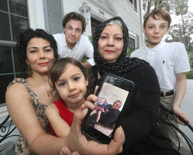 Dr. Asal Johnson with her 3-year-old daughter, Arianna, and her mother, Nasrin Afshoon, hold a cellphone with a photograph of Johnson's dad, Ahmad Mohammadi, with Johnson's husband, Allen, and her stepson, James, Friday, Feb. 19, 2021, at their DeLand home. Mohammadi has been stuck in Iran since 2018 and the family has been trying to get him to the United States.