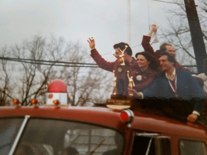 Monmouth basketball coaches Greg Dillard (left), Mike Mueller (right) and Dan Hogan (behind) ride into Monmouth on a fire truck, sporting the Class A state runner-up trophy. [SUBMITTED PHOTO]