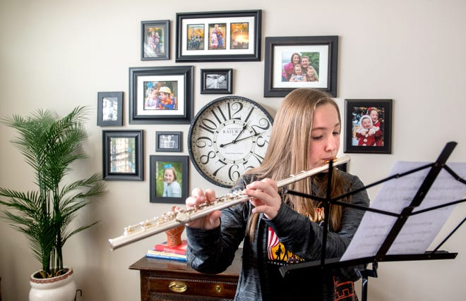 Family photos cover the wall behind Elsa Olmstead, 15, as she plays her flute at her Washington home. The Washington Community High School freshman is one of five Peoria-area high school band members was recently selected to perform as part of the Bands of America in the 2022 Rose Bowl Parade.