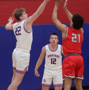 Moberly junior Brandan Milcik (#22) reaches to contest a jump shot released by Mexico's Isaiah Reams while Milcik's teammate Dominic Stoneking watches Friday night. Reams scored 20 points to help the Bulldogs defeat the Spartans 73-56.