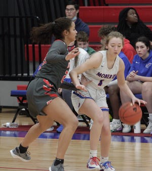 Lauren Powell, a Moberly junior guard, dribbles to her right toward the top of the key Friday while being defended by Mexico's Mya Miller. Powell and the Lady Spartans dropped a hard-fought 65-60 overtime home loss to their conference rival.