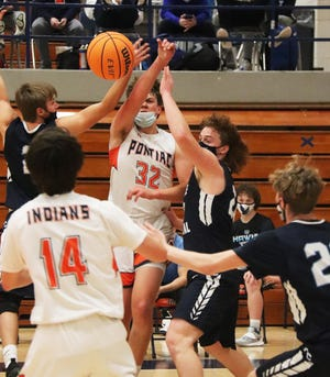 Pontiac's Logan Barnett (32) gets a pass away to teammate Matt Murphy during Friday's Illini Prairie Conference basketball game with Prairie Central. Trying to defend for teh Hawks are Trey Bazzell, left, and Cooper Palmore.