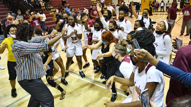 The Palm Beach Lakes Rams celebrate their regional finals win after defeating Boca, 59-44. Players gather around head coach Cassandra Rahming, who jams with a couple of victory dance moves.
