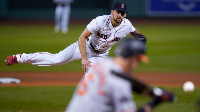 Boston Red Sox starting pitcher Nathan Eovaldi watches a throw to a Baltimore Orioles batter during the first inning of a baseball game in Boston, Sept. 23, 2020, at Fenway Park.
