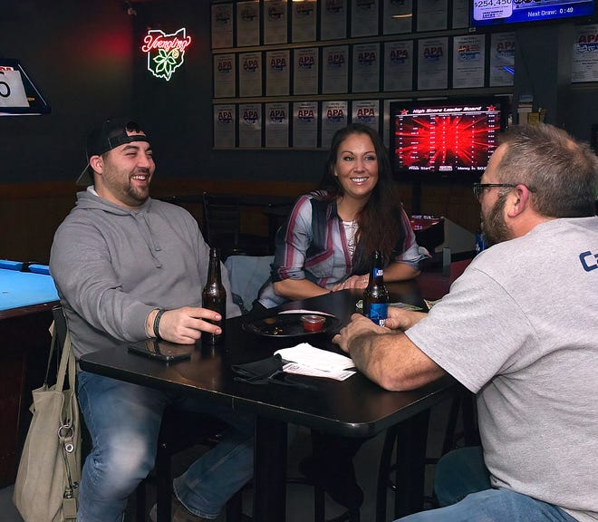 Drew and Justina Zakrajsek of Streetsboro enjoy a beer with Bill Scharra, right, of Mantua, at Chuggers in Streetsboro.
