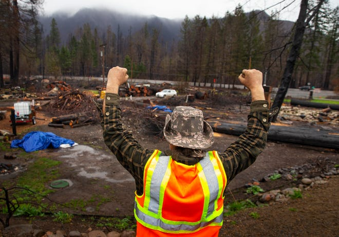 Blue River resident Clinton Roman pumps his fists in the air as volunteers arrive to help in the cleanup of the mess left behind after the Holiday Farm Fire last year.