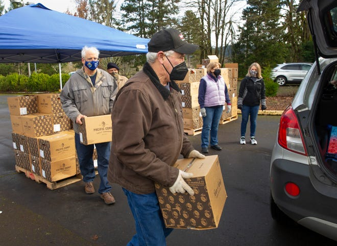 Rick Davies, center, joins a crew of volunteers in distributing food from the parking lot of St. Jude Catholic Church in Eugene Saturday, Feb. 20, 2021.