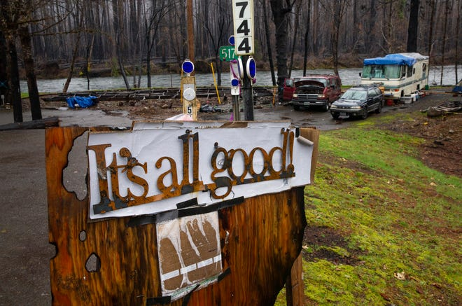 """A metal sign salvaged by Andrew Carrino from the devastation of his family's property at Blue River  takes on a new meaning as a sign along Highway 126. """"Things move on. We'll be alright,"""" said Carrino during a break from working on the property."""