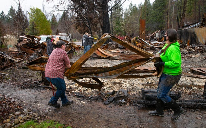 Dozens of volunteers work to remove debris from Blue River over the weekend.