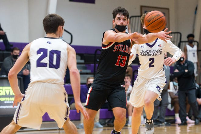 Stillman Valley's Chad Gerig passes against Rockford Lutheran's Garret Bertrand, left, in the fourth quarter of their game at Lutheran High School on Friday, Feb. 19, 2021, in Rockford. Lutheran beat Stillman Valley, 73-44.