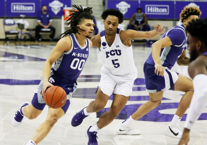 Kansas State guard Mike McGuirl (00) drives past TCU's Chuck O'Bannon Jr. (5) during the first half Saturday at Schollmaier Arena in Fort Worth, Texas.