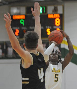 Salina South's Darell Evans (5) puts up a 3-pointer while being guarded by Newton's Tanner Dorrell (4) during the first period of the game at Salina South on Friday.