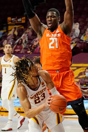Minnesota's Brandon Johnson (23) eyes the basket as Illinois' Kofi Cockburn (21) hovers over him in the first half, Saturday in Minneapolis. [Jim Mone/The Associated Press]