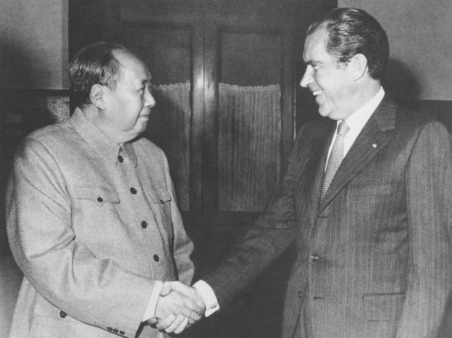 In this Feb. 21, 1972, photo, Chinese communist party leader Mao Zedong and U.S. President Richard Nixon shake hands as they meet in Beijing. Nixon's visit marked the first time an American president visited China.