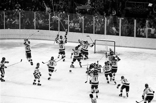 In this Feb. 22, 1980, photo, members of the U.S. ice hockey team rush toward goalie Jim Craig after their 4-3 upset win over the Soviet Union in a medal round match at the Winter Olympics in Lake Placid, New York. Some of the U.S. players shown are Mark Johnson (10); Eric Strobel (19); William Schneider (25); David Christian (23); Mark Wells (15); Steve Cristoff (11); Bob Suter (20) and Philip Verchota (27).