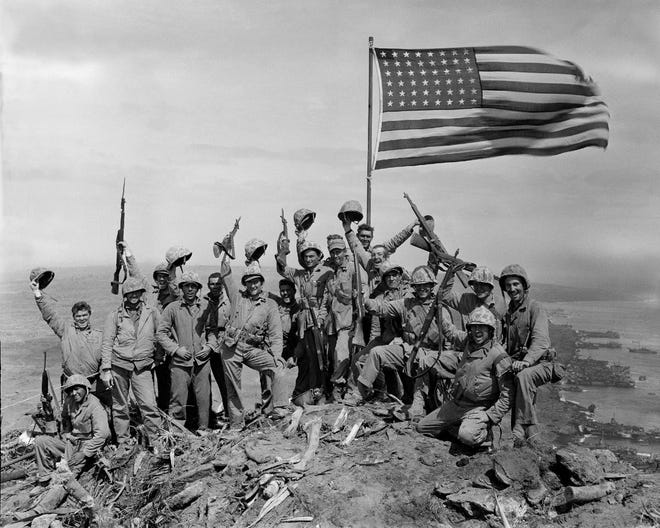 U.S. Marines of the 28th Regiment, 5th Division, cheer and hold up their rifles after raising the flag atop Mount Suribachi on Iwo Jima, a volcanic Japanese island, on Feb. 23, 1945, during World War II.