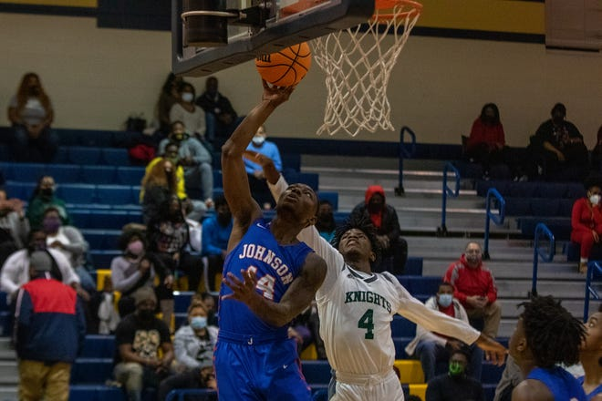 Johnson's Micah Johnson (14) shoots a layup as Windsor Forest's Abasi Scott (4) attempts to block the shot. Johnson won 60-53 for the Region 3-3A tournament title on Friday night at Beach High School.