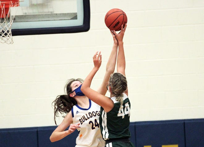 Paige Walton blocks a shot by Alexis Snodgrass in Friday night hoops action.